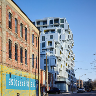 Morning sun accentuates the boxed balcony volumes, as seen looking north from Queen St. West. Photo by Scott Norsworthy.