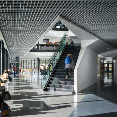 View of into the central forum of the student centre, with highlighting the feature stair, and throughway pedestrian connection that extends through the building. Photo by Andrew Latreille.